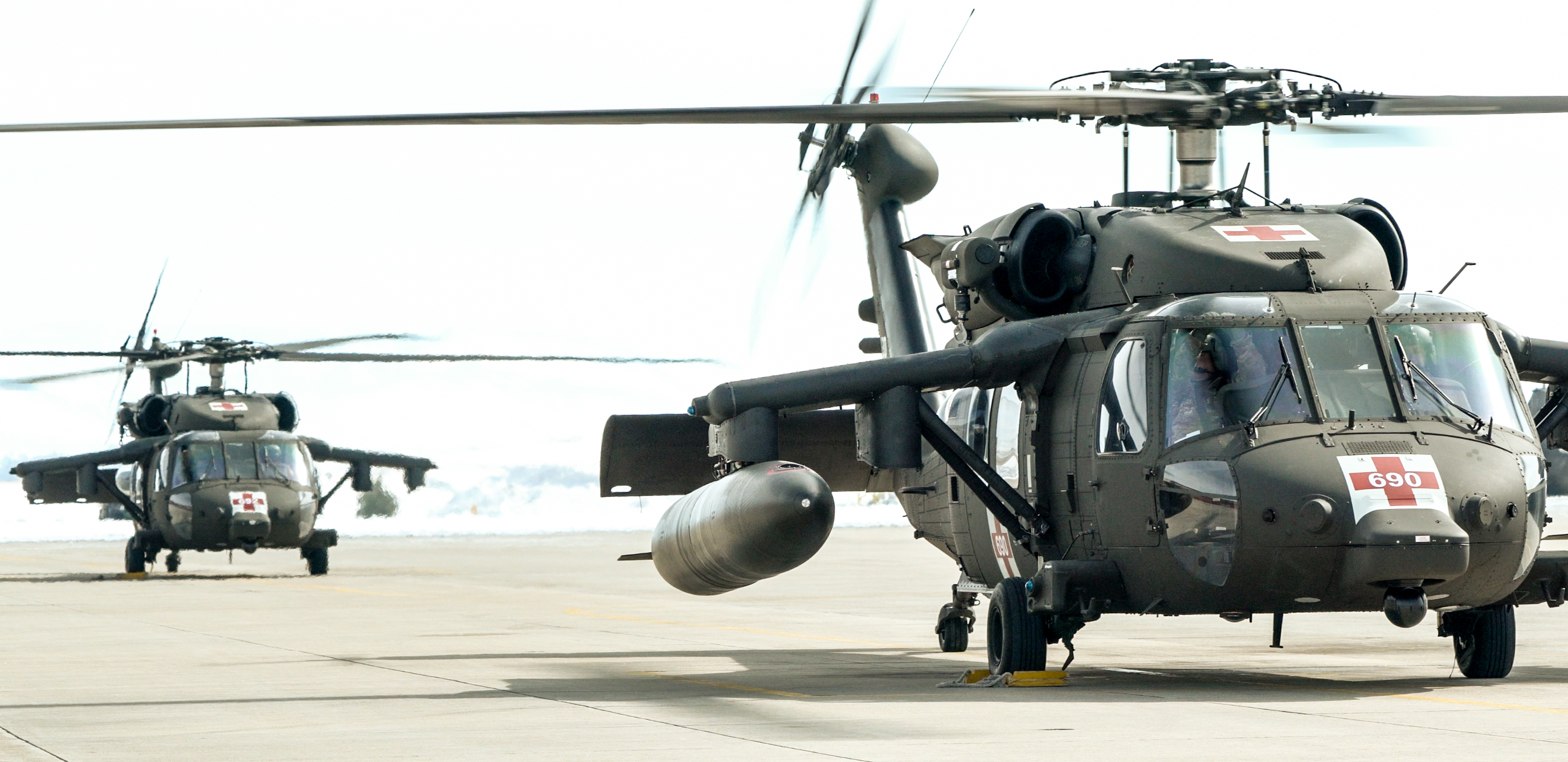 Two Blackhawk helicopters on the tarmac for simulation training