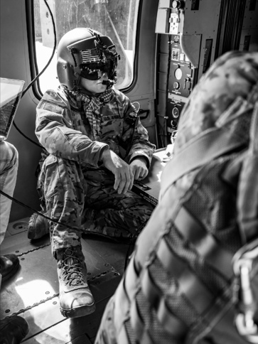 Soldier watching unit perform blood transfusion