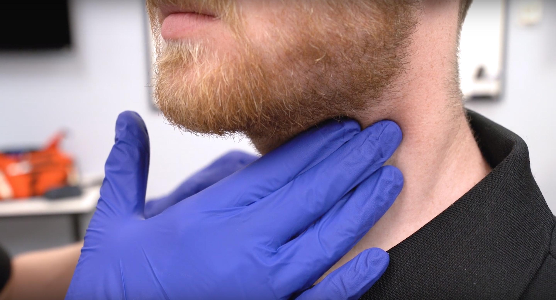 Palpating carotid artery pulse